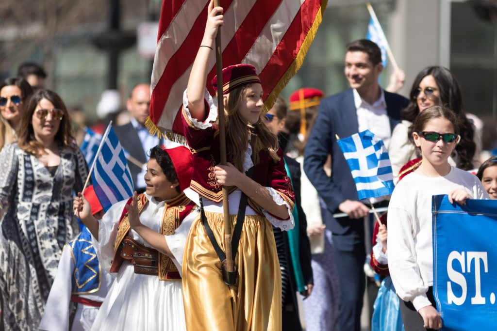 Chicago, Illinois, USA - April 29, 2018 Young greek woman wearing traditional clothing carrying the USA flag during the Greek Independence Day Parade