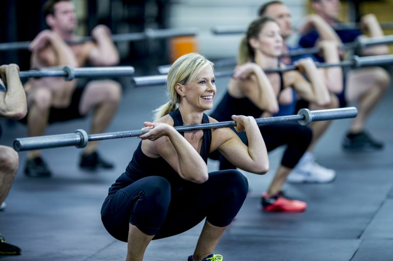 A group of adults are taking a fitness class together in a gym. They are wearing athletic clothes. They are squatting while holding a barbell.