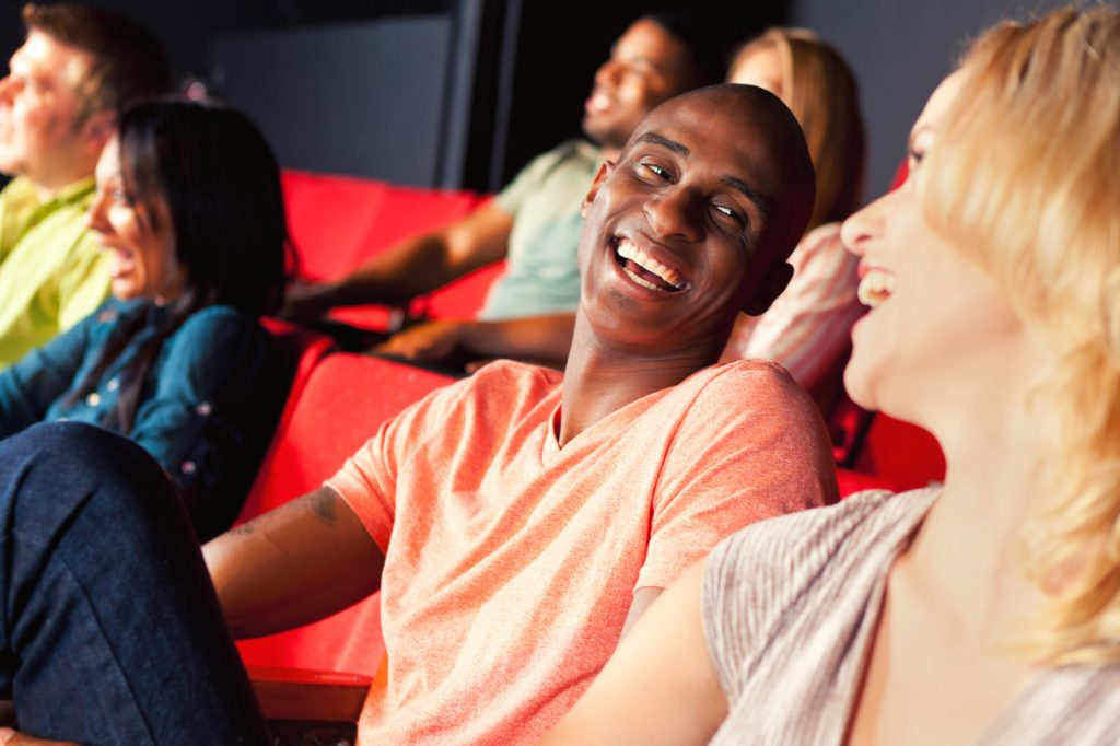 Handsome African American man smiles and laughs while watching a movie with his girlfriend in a movie theater.