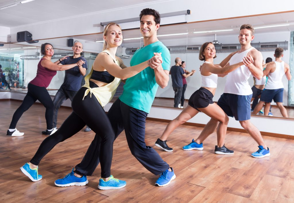 Young men and women dancing a salsa o bachata at a dance hall. Dances classes in a dance studio