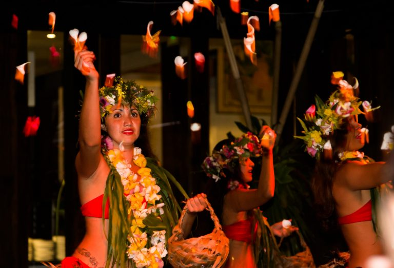 Polynesian dancers with flower petals at nighttime event