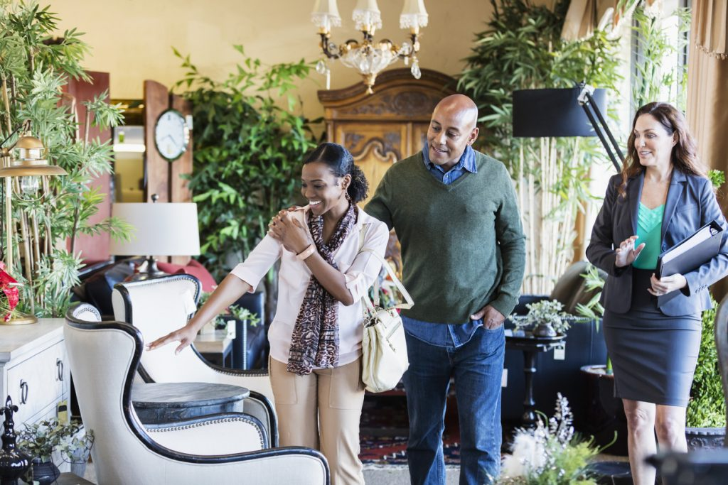 An African-American couple, the woman in her 30s and the man in his 40s, shopping in a furniture store or home accessories store, being helped by a saleswoman or interior designer.