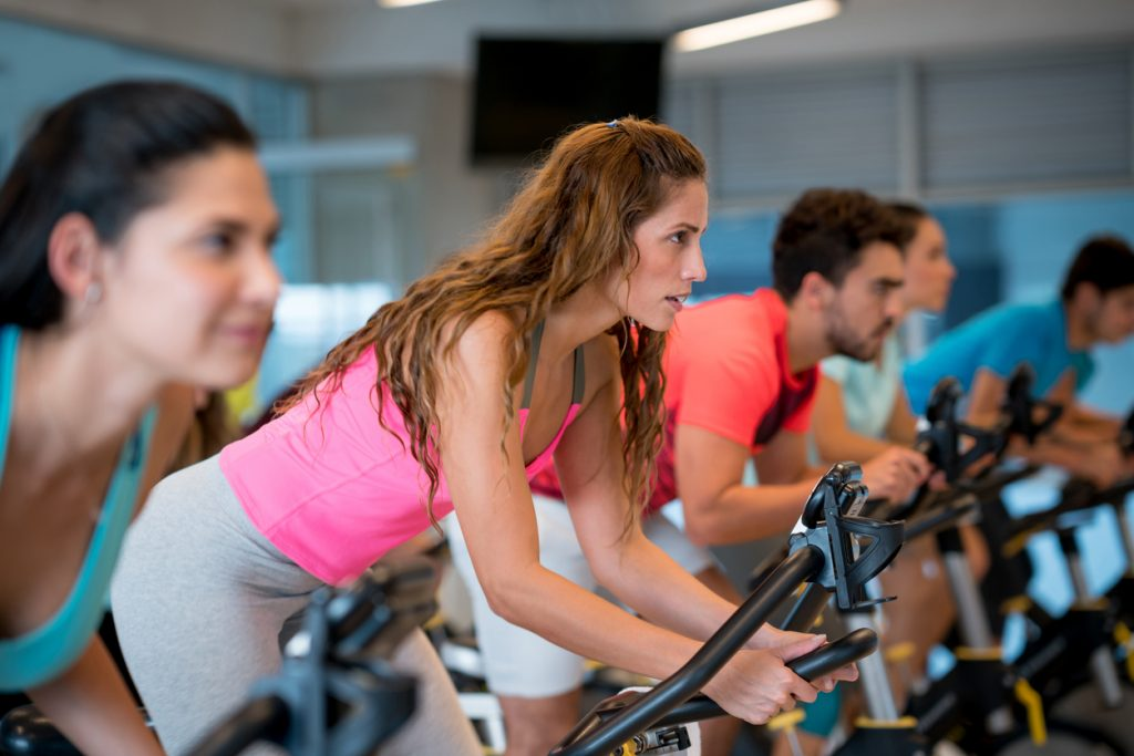 Beautiful woman in a spin class at the gym and everyone looking very focused