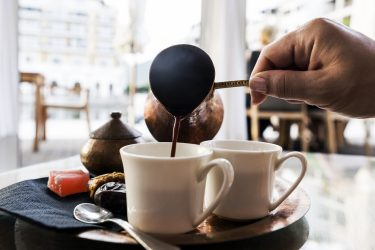 Turkish Coffee is pouring in coffee cup. Turkish coffee shops in Chicago