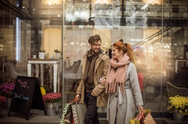 Young couple walking and shopping holding bags and wearing warm clothing.