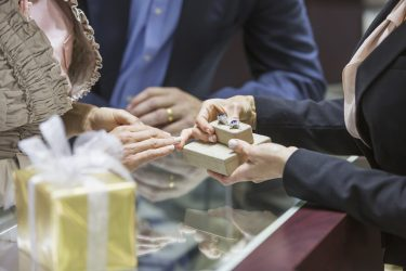 Cropped view of a saleswoman in a local jewelry store helping a mature couple, showing the customers a pair of rings from the display case.