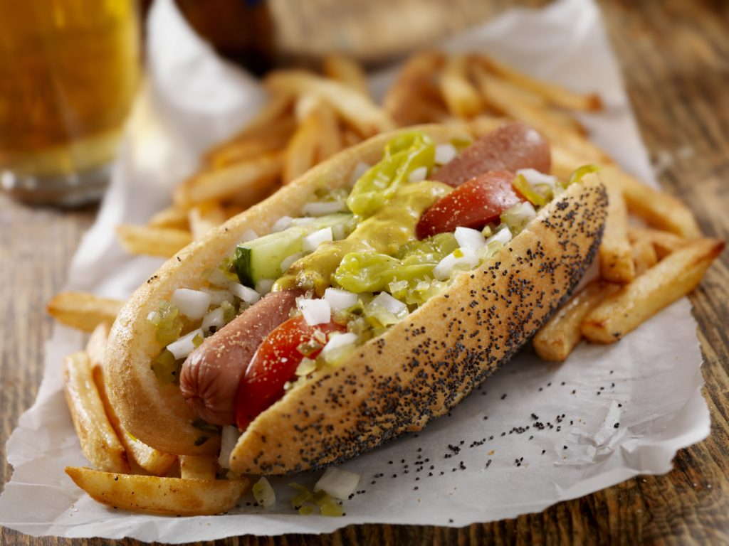 A Classic Chicago Dog with Fries and a Beer - The Chicago Dog has a Steamed Poppyseed Bun, Fresh Tomatoes, Diced Onions, Neon Green Relish,Peppers,Pickle, Yellow Mustard and a Dash of Celery Salt