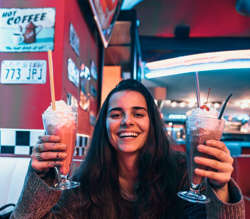 smiling woman holding two milkshakes in an old-fashioned diner