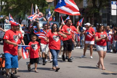 Chicago, Illinois, USA - June 16, 2018: The Puerto Rican People's Parade, Puerto Rican people carrying puerto rican flags celebrating during the parade