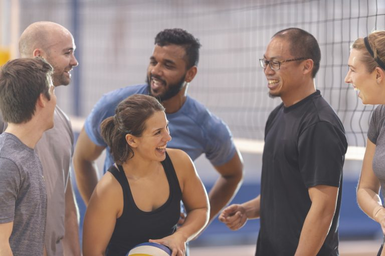Several people in sportswear are talking together in front of a volleyball net in an indoor court. One woman in the middle is holding a volleyball. Co-ed adult volleyball leagues