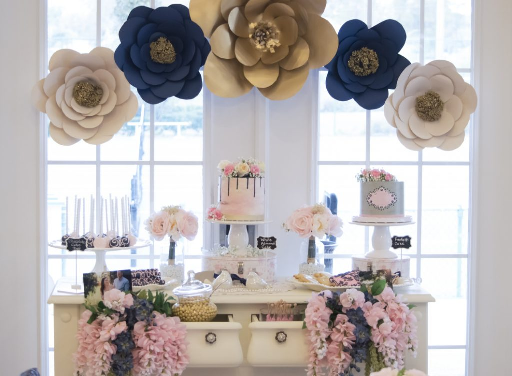 The decorated dessert table at a bridal show with cakes, chocolate covered pretzels, and cake pops.