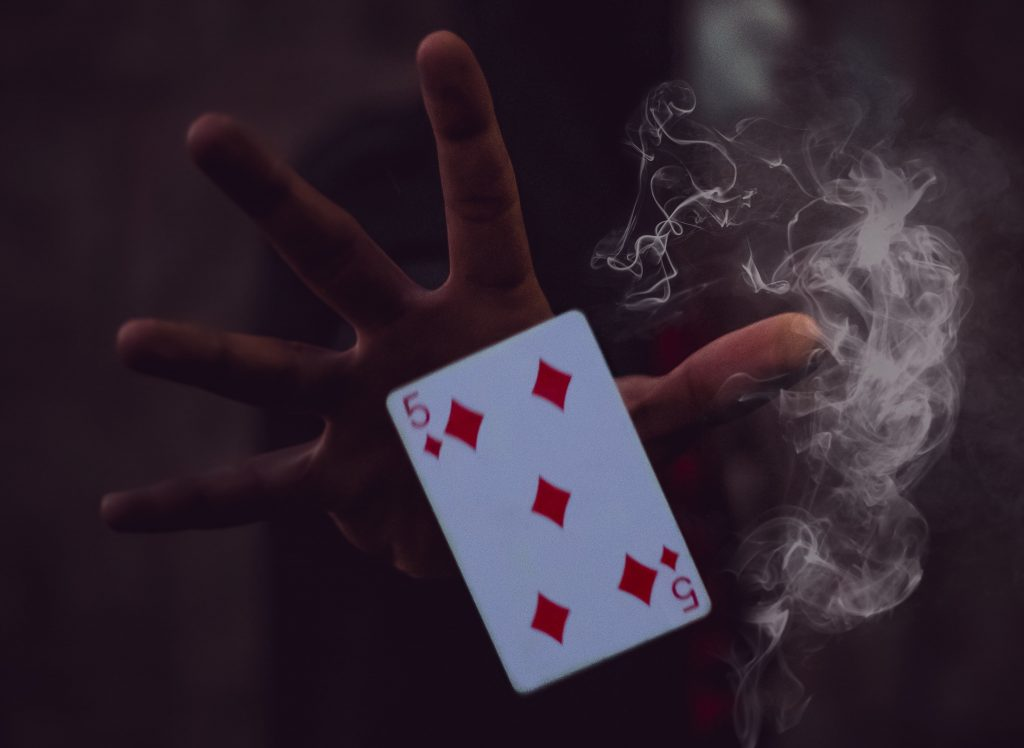 Five of diamonds in a magician's hand with smoke in a magic show