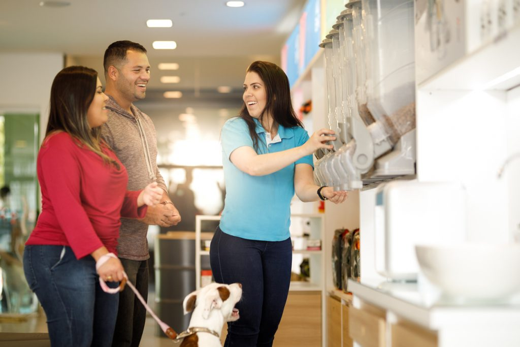 Employee assisting customers with their dog at a pet store