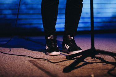 close up on a comedian's shoes on sage doing improv at local comedy clubs
