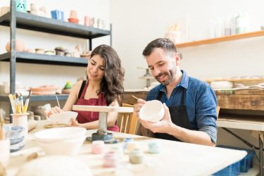 Mid adult couple smiling while doing creative painting on bowls in a ceramics class in a pottery workshop